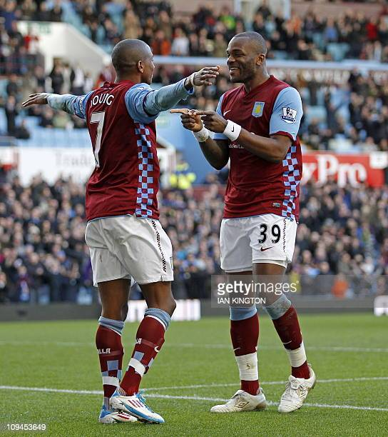 Aston Villa's English midfielder Ashley Young celebrates scoring the opening goal with English striker Darren Bent during the English Premier League...
