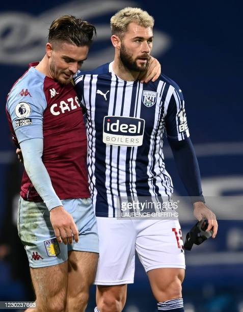 Aston Villa's English midfielder Jack Grealish and West Bromwich Albion's English striker Charlie Austin embrace after the English Premier League...