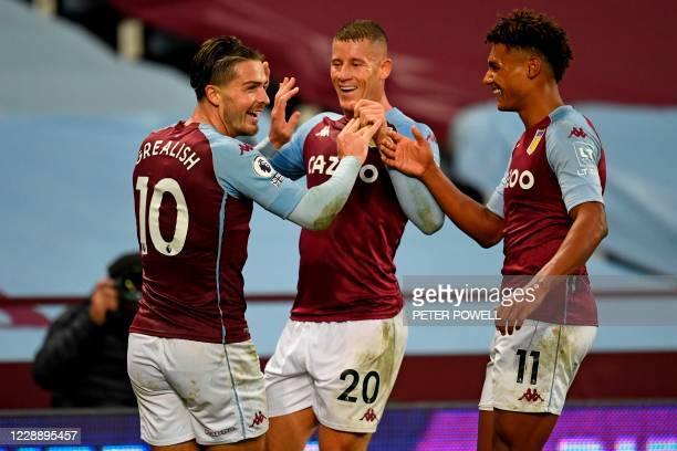 Aston Villa's English midfielder Jack Grealish celebrates with Aston Villa's English midfielder Ross Barkley and Aston Villa's English striker Ollie...