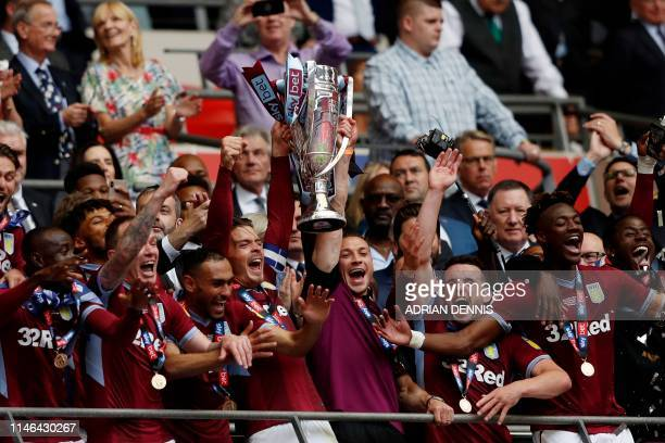 Aston Villa's English midfielder Jack Grealish celebrates with the trophy after the English Championship play-off final football match between Aston...