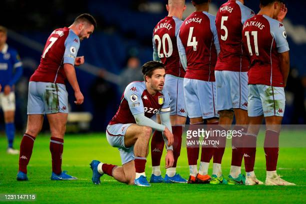 Aston Villa's English midfielder Jack Grealish kneels behind the wall to defend against the low shot from a free kick during the English Premier...