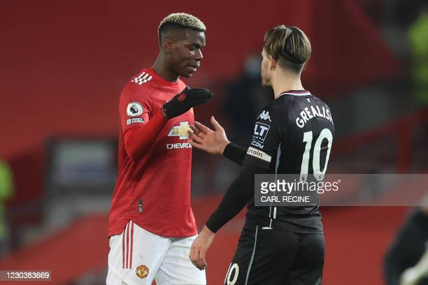 Aston Villa's English midfielder Jack Grealish shakes hands with Manchester United's French midfielder Paul Pogba as they leave the pitch after the...
