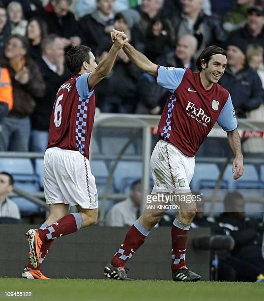 Aston Villa's English midfielder Stewart Downing celebrates scoring his goal with French midfielder Robert Pires during the English Premier League...