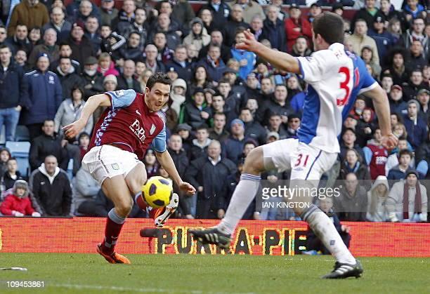 Aston Villa's English midfielder Stewart Downing scores their third goal during the English Premier League football match between Aston Villa and...