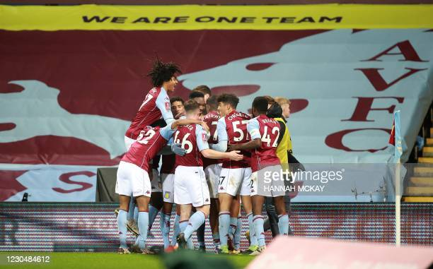 Aston Villa's English striker Louie Barry is mobbed by teammates after scoring the equalising goal during the English FA Cup third round football...