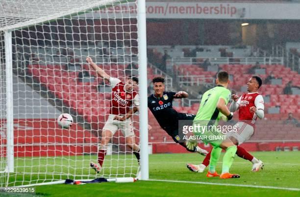 Aston Villa's English striker Ollie Watkins scores his team's second goal past Arsenal's Scottish defender Kieran Tierney and Arsenal's German...