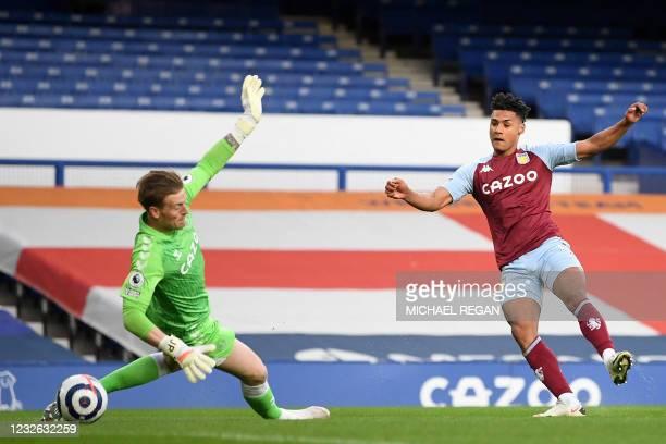 Aston Villa's English striker Ollie Watkins shoots past Everton's English goalkeeper Jordan Pickford to score the opening goal of the English Premier...
