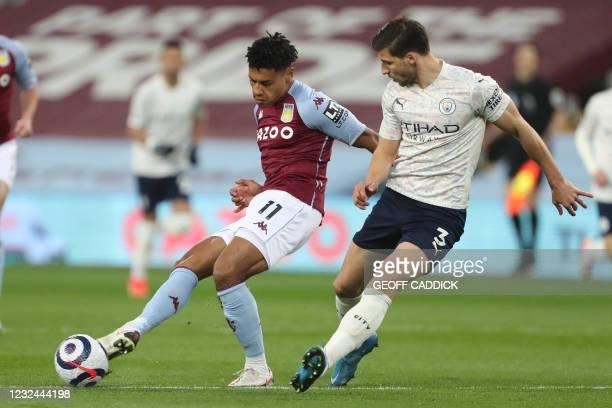 Aston Villa's English striker Ollie Watkins vies with Manchester City's Portuguese defender Ruben Dias during the English Premier League football...