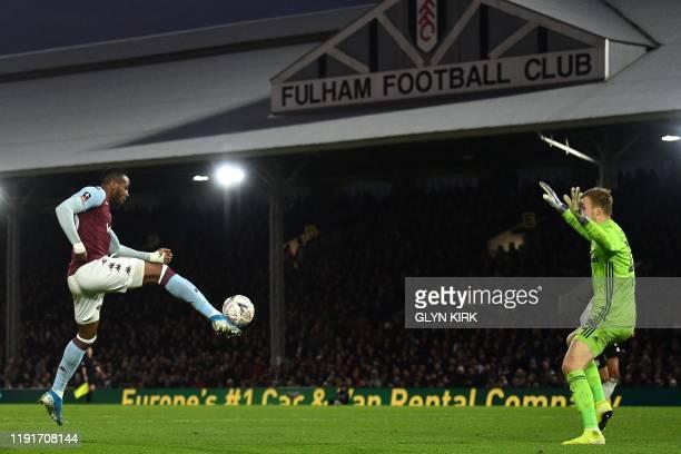 Aston Villa's Ivorian striker Jonathan Kodjia chips the ball over Fulham's Slovakian goalkeeper Marek Rodak in the build-up to their first goal...