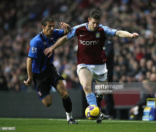 Aston Villa's James Milner is challenged by Middlesbrough's Gary O'Neil during the Premiership match at Villa Park in Birmingham England on November...
