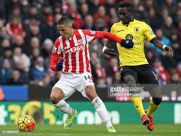 Aston Villa's Senegalese midfielder Idrissa Gueye vies with Stoke City's Dutch midfielder Ibrahim Afellay during the English Premier League football...