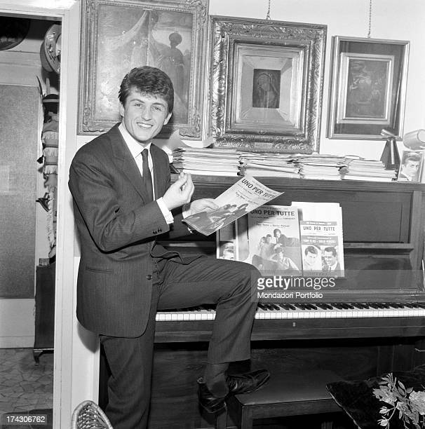 Astonished the singer Elio Cesari known with his nom de plume Tony Renis sits posing his leg on the piano in a living room on the music stand there...