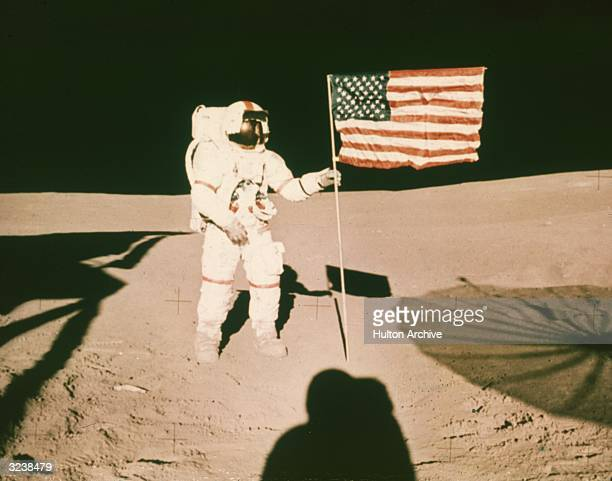 Astronaut Alan B Shepard holds the pole of a US flag on the surface of the moon during the Apollo 14 mission