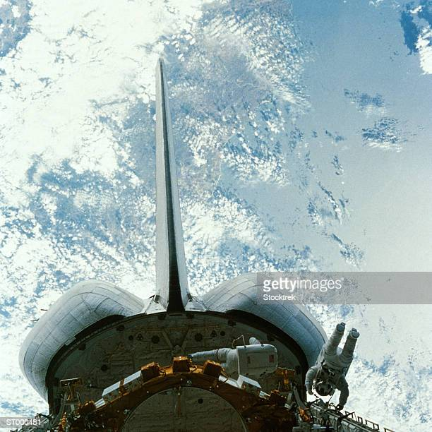 Astronaut and the Space Shuttle and Earth Below