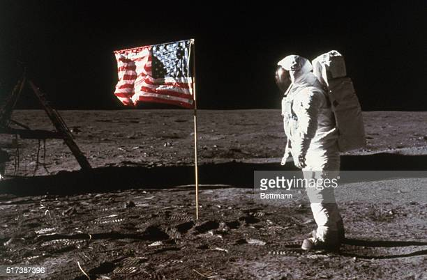 Astronaut Buzz Aldrin lunar module pilot stands beside an American flag placed on the moon during Apollo 11 extravehicular activity He is...