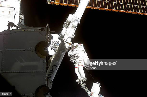 Astronaut Chris A Hadfield STS100 mission specialist representing the Canadian Space Agency stands on a Canadianbuilt robot arm to work with another...