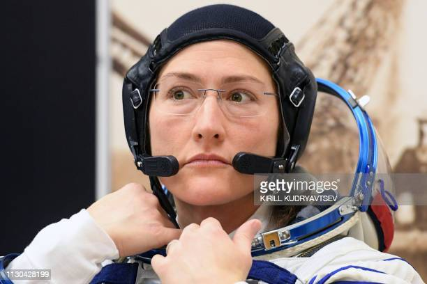 NASA astronaut Christina Hammock Koch a member of the International Space Station expedition 59/60 looks on as her spacesuit is tested prior to the...