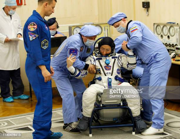 NASA astronaut Christina Hammock Koch a member of the International Space Station expedition 59/60 is helped by specialists as her spacesuit is...