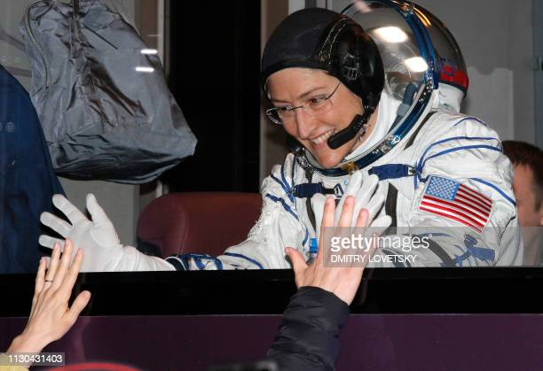 NASA astronaut Christina Hammock Koch a member of the International Space Station expedition 59/60 gestures from inside a bus shortly before the...