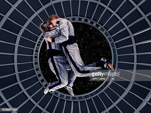 astronaut couple embracing in space station (digital composite) - astronaut stock pictures, royalty-free photos & images