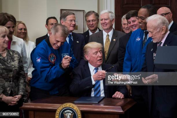 Astronaut Dave Wolf left pretends to grab a pen as President Donald Trump hands it to former astronaut Buzz Aldrin after signing an executive order...
