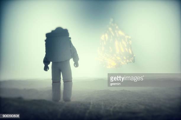 Astronaut discovering strange glowing alien object