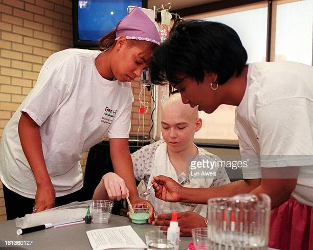 Astronaut Dr Mae C Jamison helps Angie Hancock a patient at Children's Hospital in Denver to do a science experiment called 'Sticky Icky' Manual High...