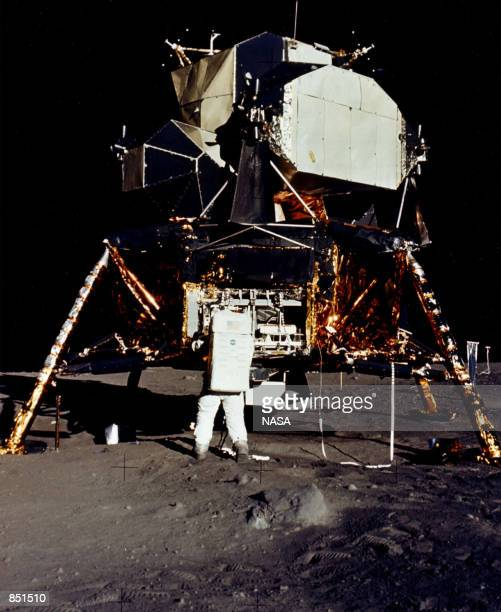 Astronaut Edwin E Aldrin Jr Lunar Module Pilot removes scientific experiment packages from a stowage area in the Lunar Module's descent stage Man's...