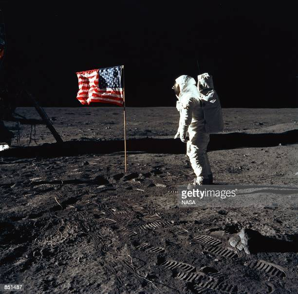Astronaut Edwin E. Aldrin, Jr., the lunar module pilot of the first lunar landing mission, stands next to a United States flag July 20, 1969 during...