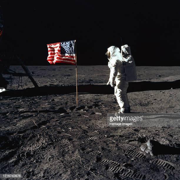 """Astronaut Edwin E. """"Buzz"""" Aldrin, Jr., beside the U.S. Flag during an Apollo 11 moon walk. The Lunar Module is on the left, and the footprints of the..."""