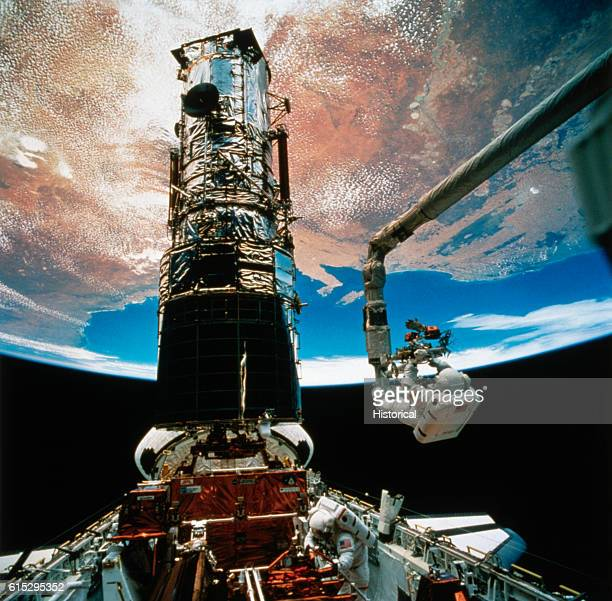 Astronaut F Story Musgrave anchored on the end of the Remote Manipulator System arm prepares to be elevated to the top of the towering Hubble Space...