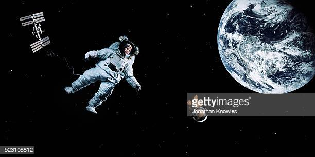 astronaut floating in space - 人工衛星 ストックフォトと画像