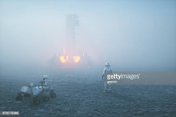 Astronaut in fog against alien object