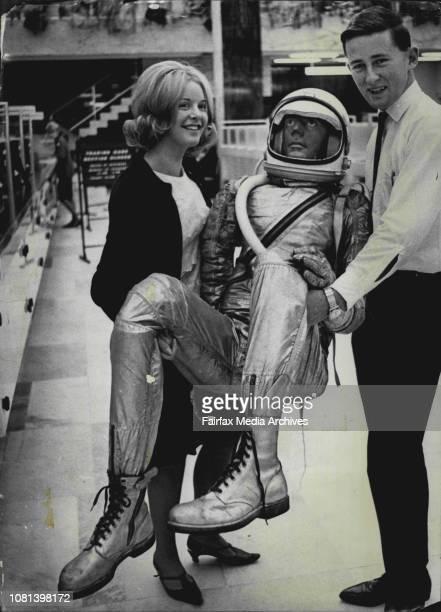 Astronaut in SydneyMiss Helen Staples of Kogarah bank machinists and teller Bill Cullen of Berowra carry a replica of a Project Mercury astronaut...