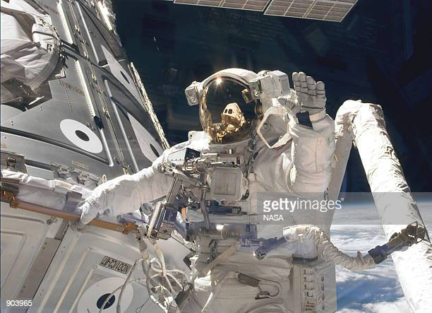 Astronaut James H Newman waves at camera as he holds onto one of the hand rails on the Unity connecting module during the early stages of a 7hour...