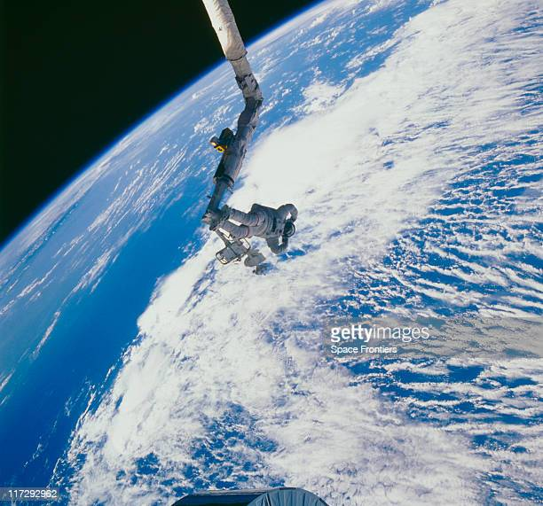 Astronaut James van Hoften on the Space Shuttle Discovery's robot arm or Remote Manipulator System as he tracks the US Navy's Syncom IV3 satellite...