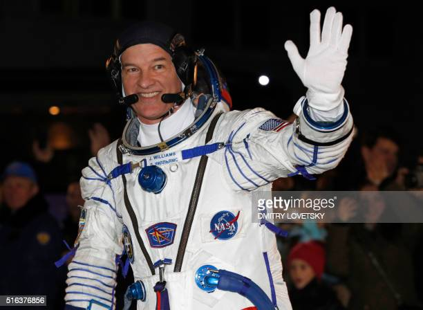 US astronaut Jeffrey Williams waves from a bus after his space suit was tested at the Russianleased Baikonur cosmodrome in Kazakhstan prior to...