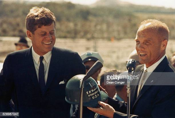 Astronaut John Glenn hands a hard hat to President John F Kennedy at Cape Canaveral in Florida Several days before Glenn became the first person to...