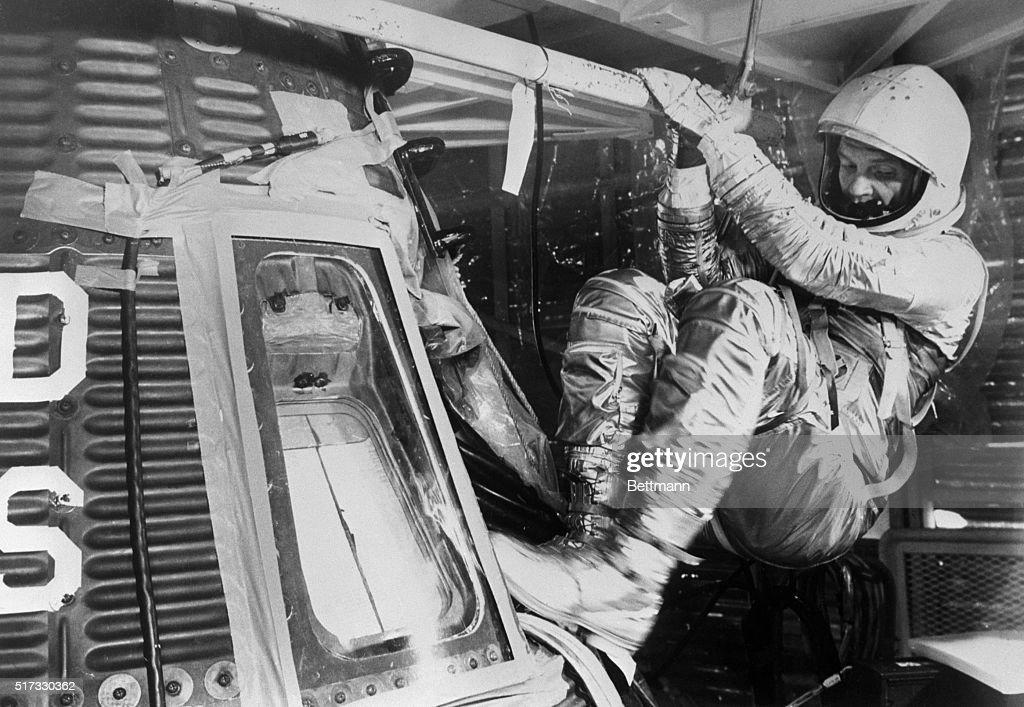 John Glenn Climbing into Space Capsule : News Photo