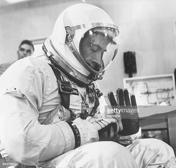 Astronaut John W Young copilot of the NASA Gemini 3 mission inspecting his spacesuit at the Complex 16 suitingup area March 23rd 1965