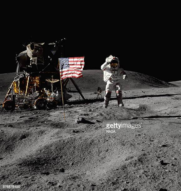 Astronaut John W Young throws a salute to the flag in Descartes Crater on the surface of the Moon The Apollo 16 lunar module Orion and lunar rover...