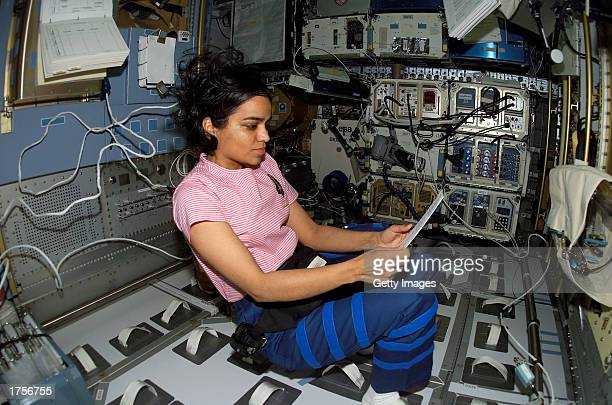 Astronaut Kalpana Chawla STS107 mission specialist looks over a procedures checklist in the SPACEHAB Research Double Module aboard the Space Shuttle...