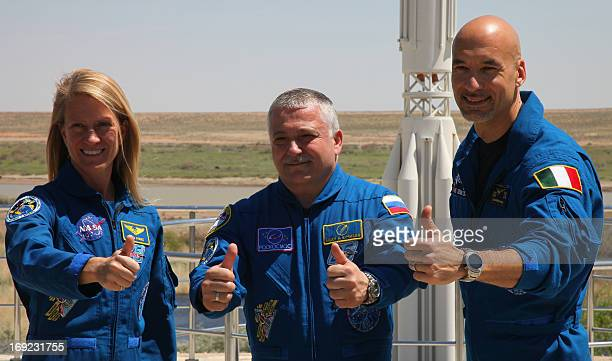 US astronaut Karen Nyberg Russian cosmonaut Fyodor Yurchikhin and European Space Agency Italian astronaut Luca Parmitano give a thumbsup as they take...