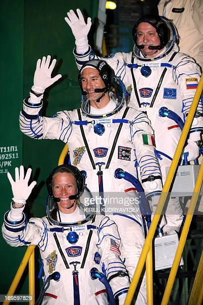 US astronaut Karen Nyberg Russian cosmonaut Fyodor Yurchikhin and European Space Agency Italian astronaut Luca Parmitano wave as they board the Soyuz...