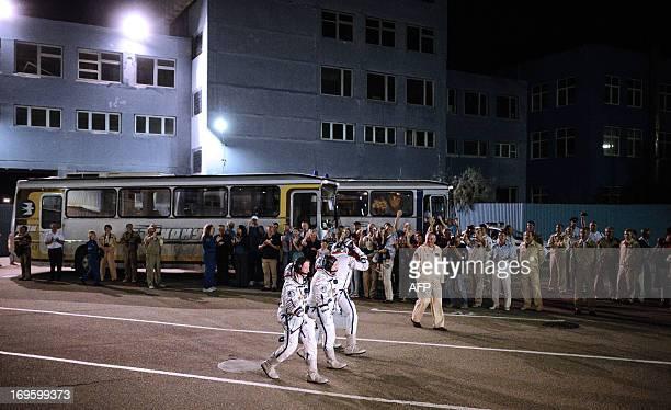 US astronaut Karen Nyberg Russian cosmonaut Fyodor Yurchikhin and European Space Agency Italian astronaut Luca Parmitano walk from their hotel to a...