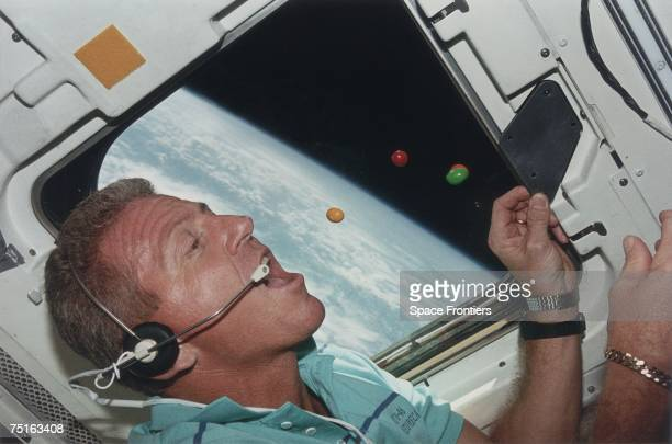 Astronaut Loren J Shriver Mission Commander of STS46 attempts to eat floating sweets on the flight deck of the shuttle Atlantis during its orbit of...