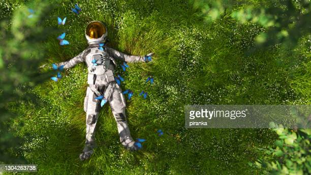 astronaut lying in the meadow - hd stock pictures, royalty-free photos & images