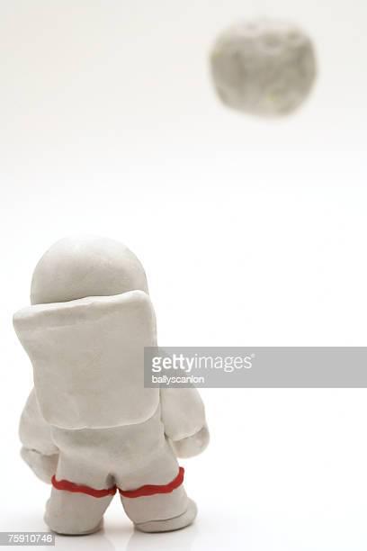 astronaut made of clay facing moon on a white background - menschliche darstellung stock-fotos und bilder