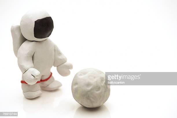 astronaut made of clay reaching for the moon - menschliche darstellung stock-fotos und bilder
