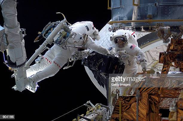 Astronaut Michael J Massimino hovers over the Space Shuttle Columbia's cargo bay while astronaut James H Newman stands nearby March 5 2002 during an...